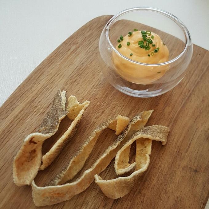 Surtopía (Crema de queso con manteca colorá y pieles de bacalao fritas)