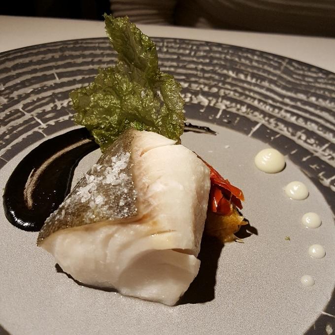Carboneras de Lu (Bacalao negro confitado, puerros, tomate semiseco, salsas de ajo negro y ajo blanco)